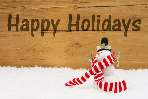 Happy holidays message, a snowman on snow with a weathered wood background and text happy holidays