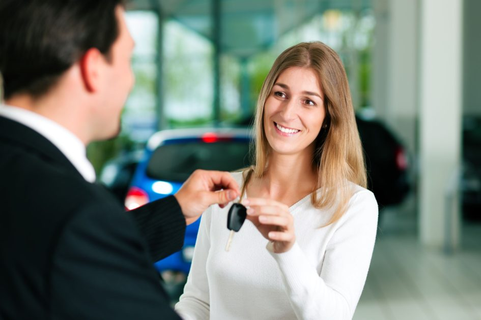 Salesman handing woman car keys