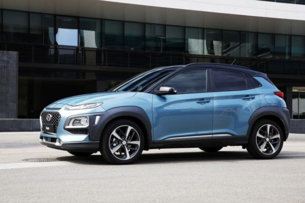 A blue all-new 2018 Hyundai Kona driving down the street.