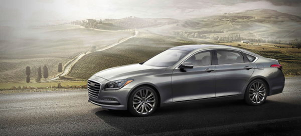 A new silver Hyundai Genesis G80 sedan driving down a misty country road.