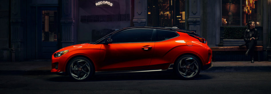 Orange 2019 Hyundai Veloster parked on street at night