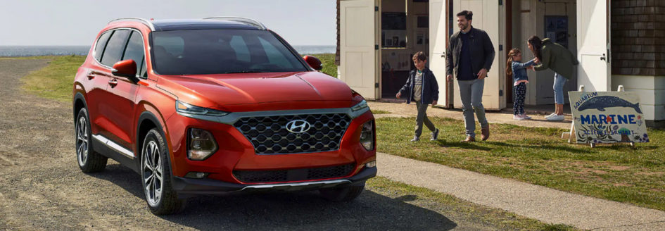 Red 2019 Hyundai Santa Fe Sport parked beachside with family next to it