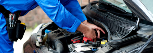 Auto mechanic under the hood of a car working on the battery